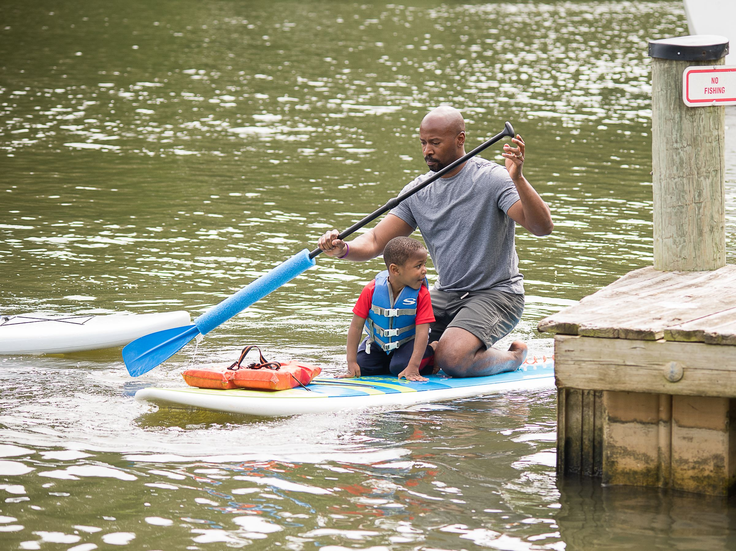 man and boy on paddleboard