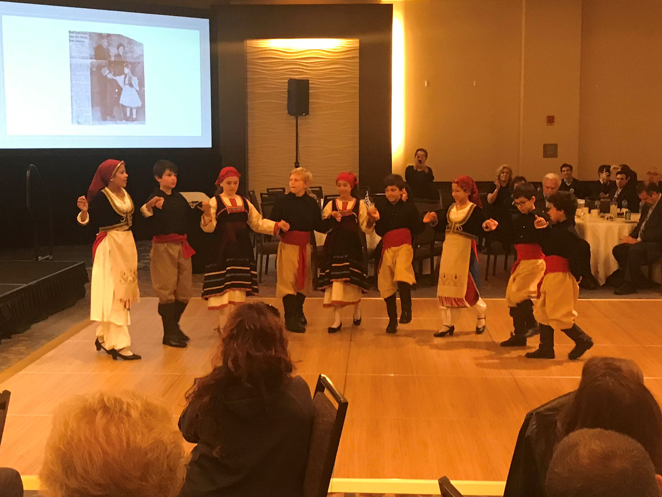 HARA Greek Dancers with picture of Queen's visit to Annapolis in background.