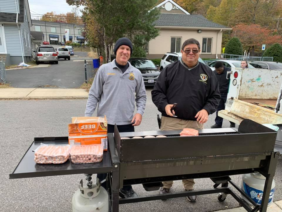 Two people stand in front of a BBQ grill.