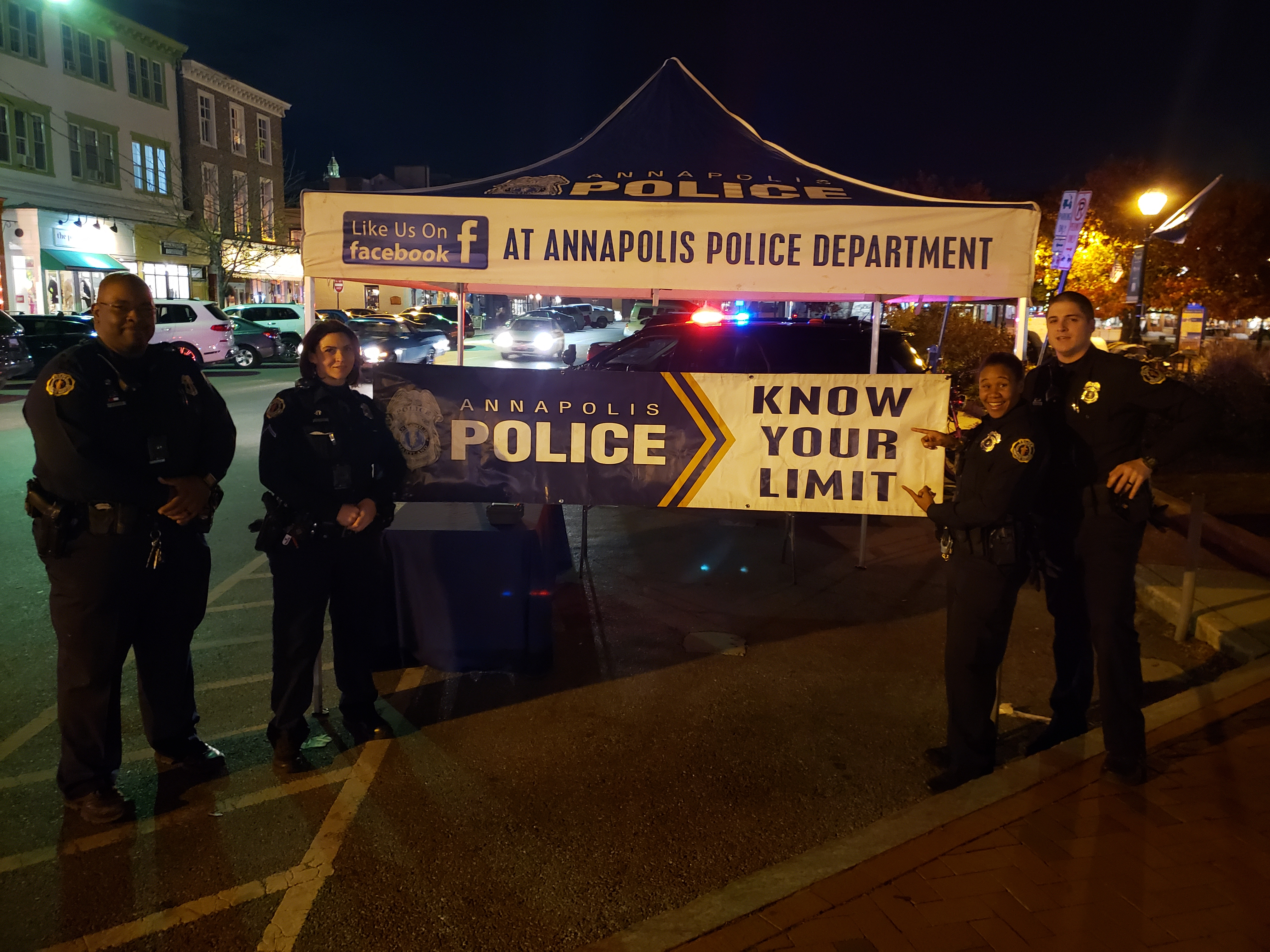 A group of uniformed police officers stands in front of a tent with a Know Your Limit banner.