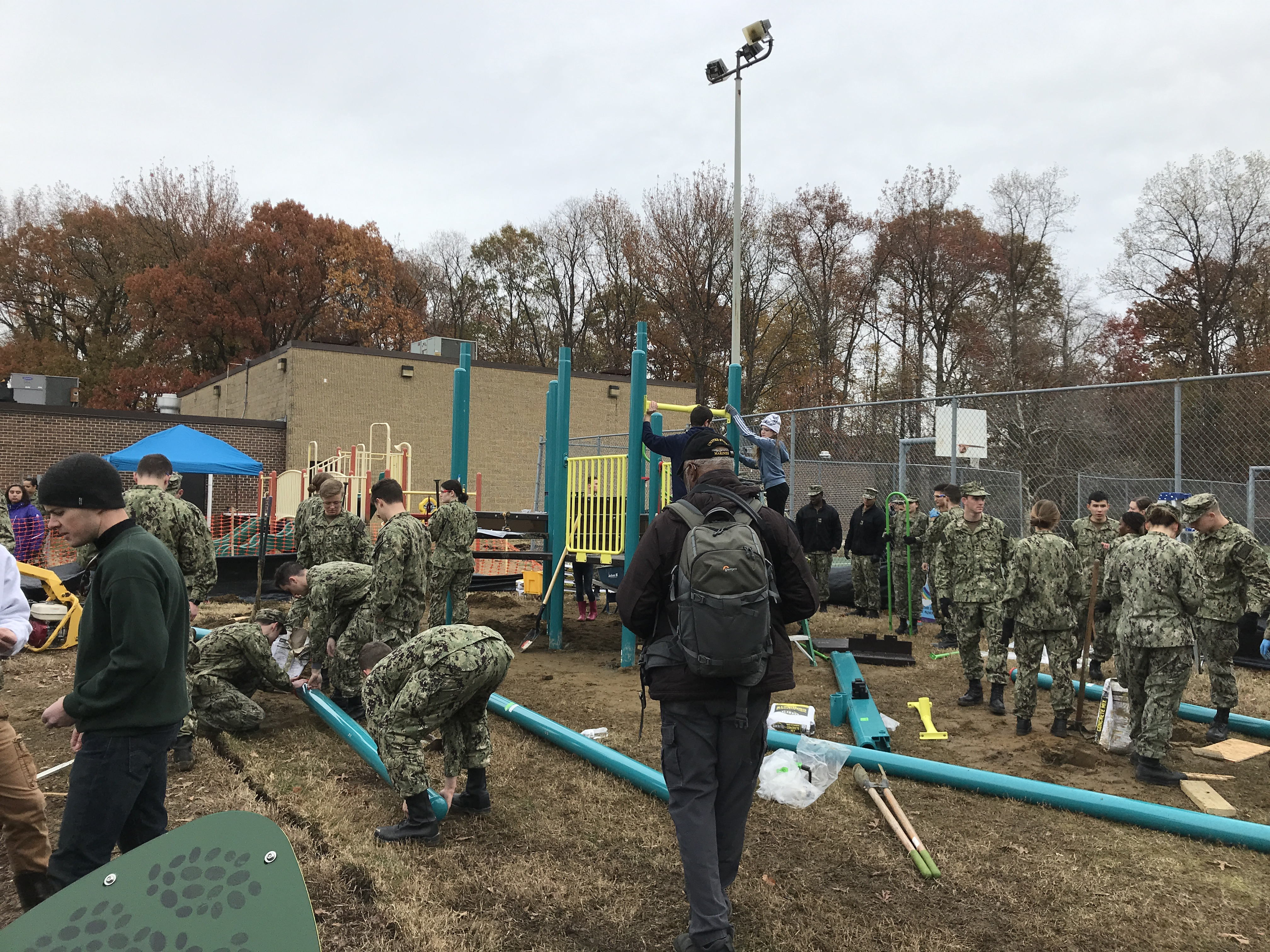 A group of uniformed Midshipmen on a playground building site.