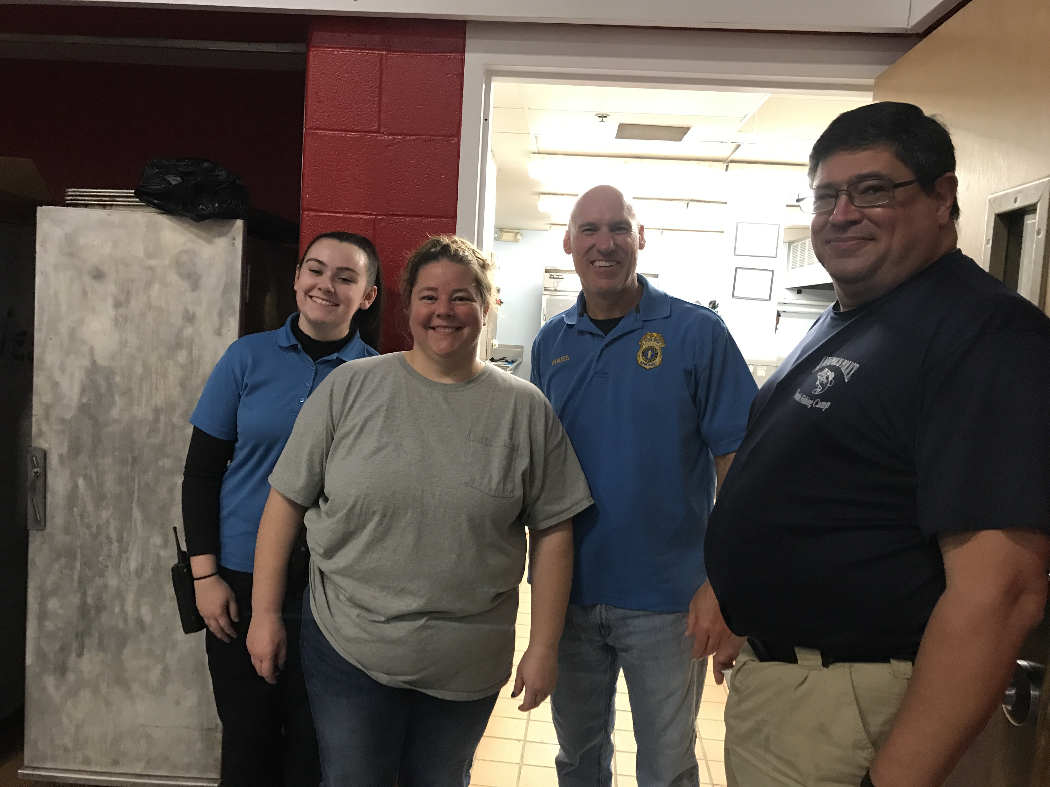 A group of police department employees stand outside a kitchen.