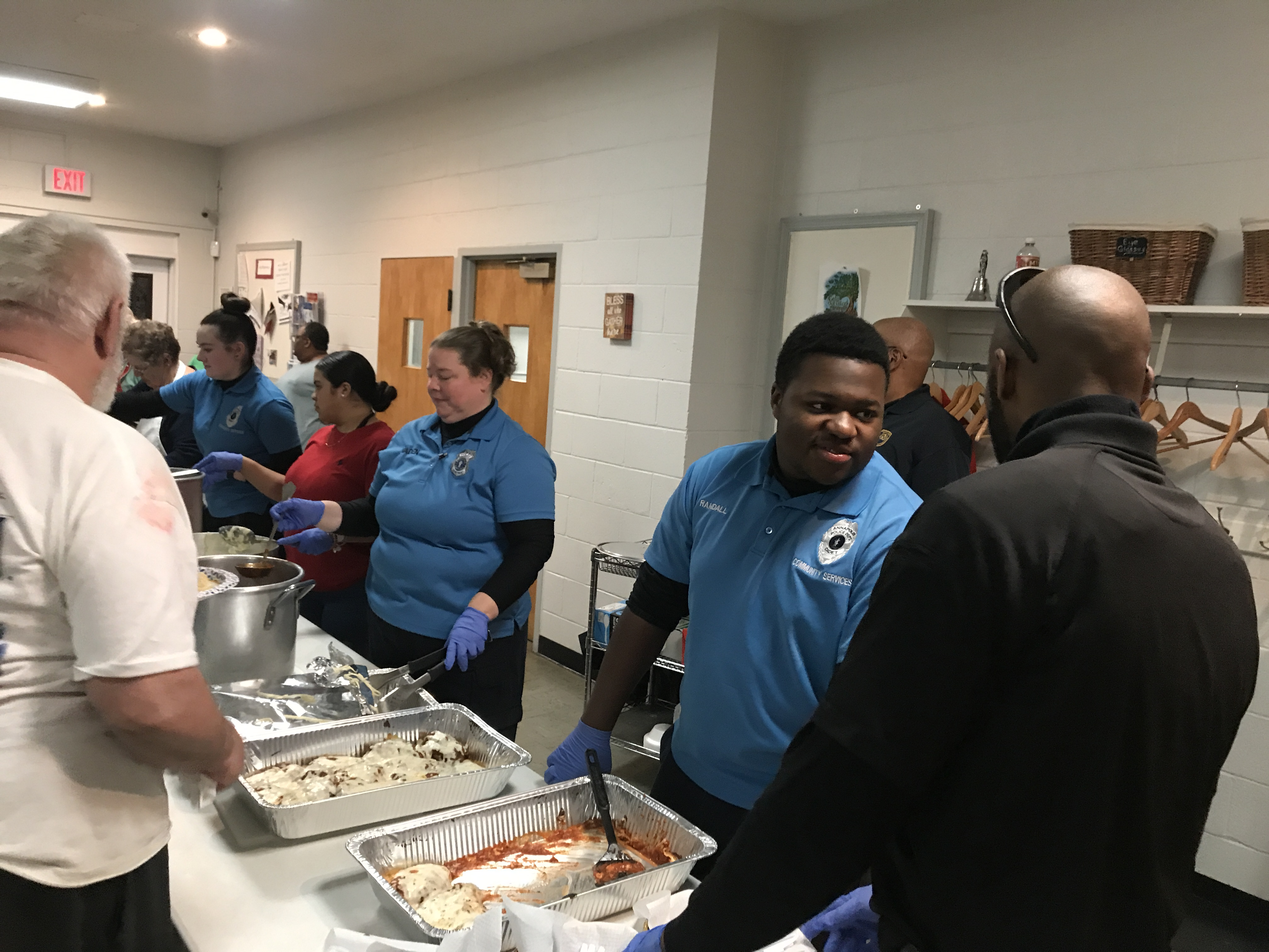 A group of police department employees stand serving food.