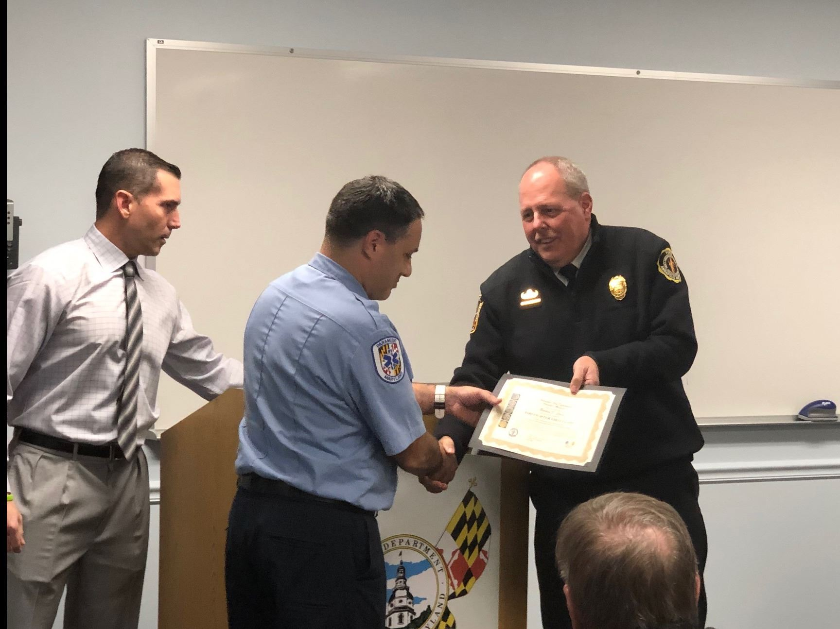Chief Remaley presenting F1C Clark his certificate while shaking hands