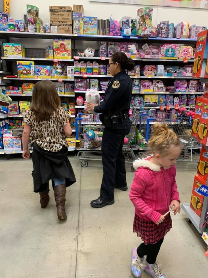 Kids shopping with a uniformed officer.