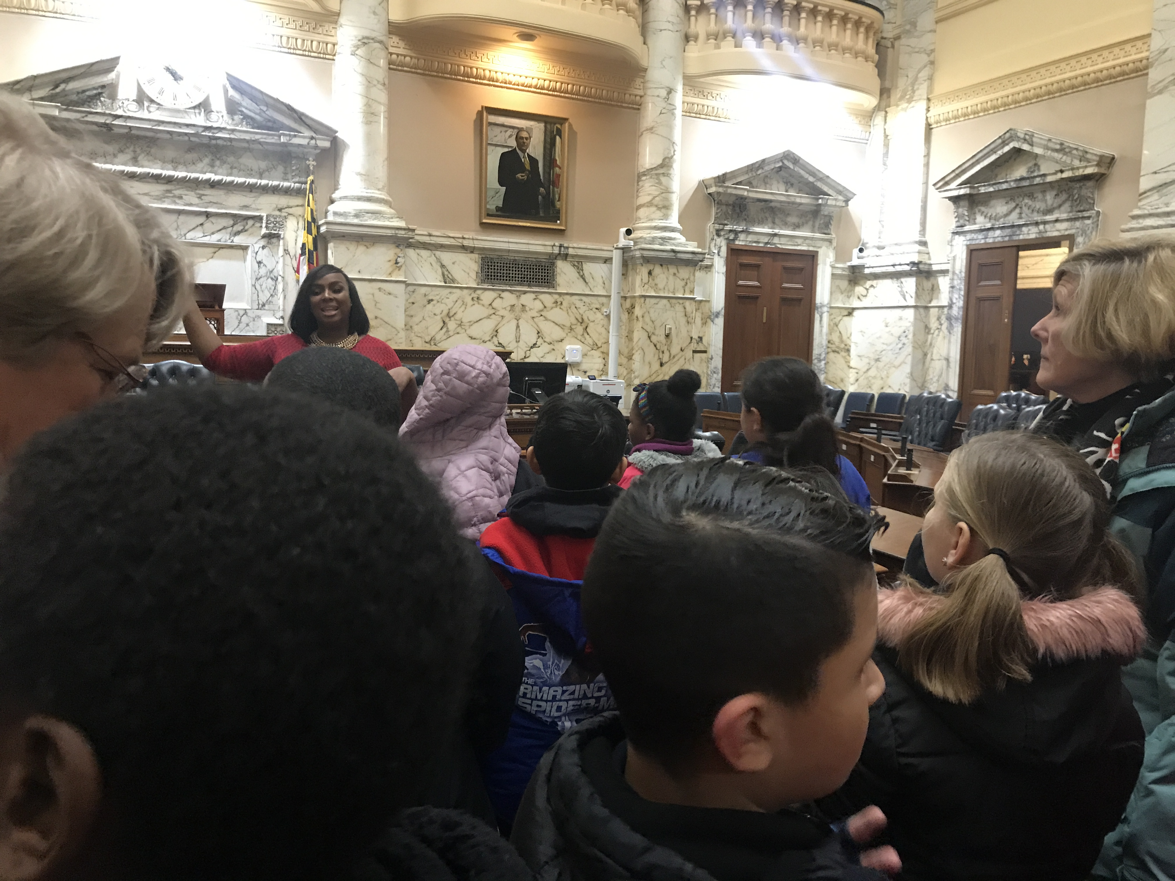 Group of children standing in the State House listening to Delegate Henson.