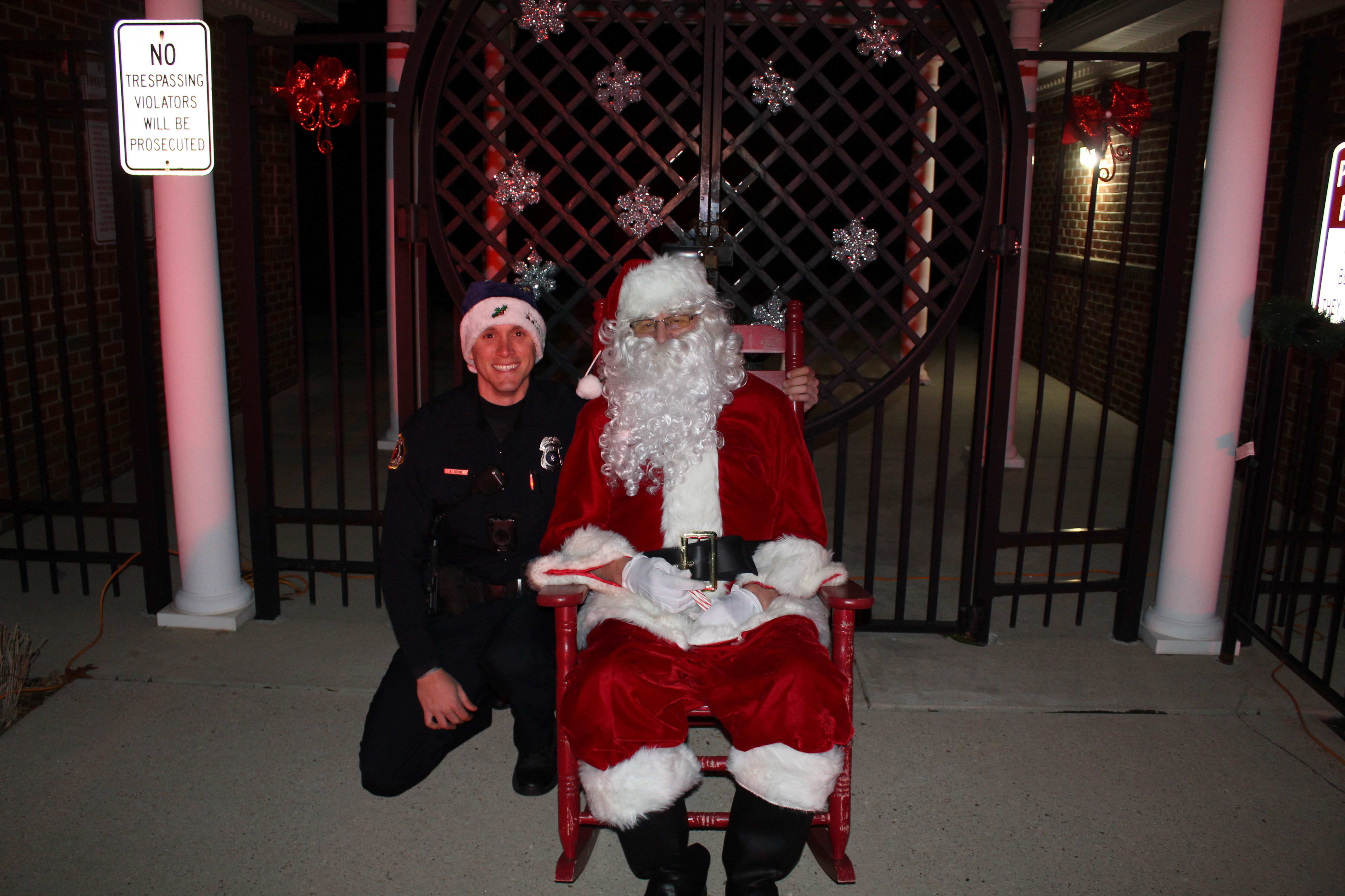 Santa sitting with police officer kneeling next to him.