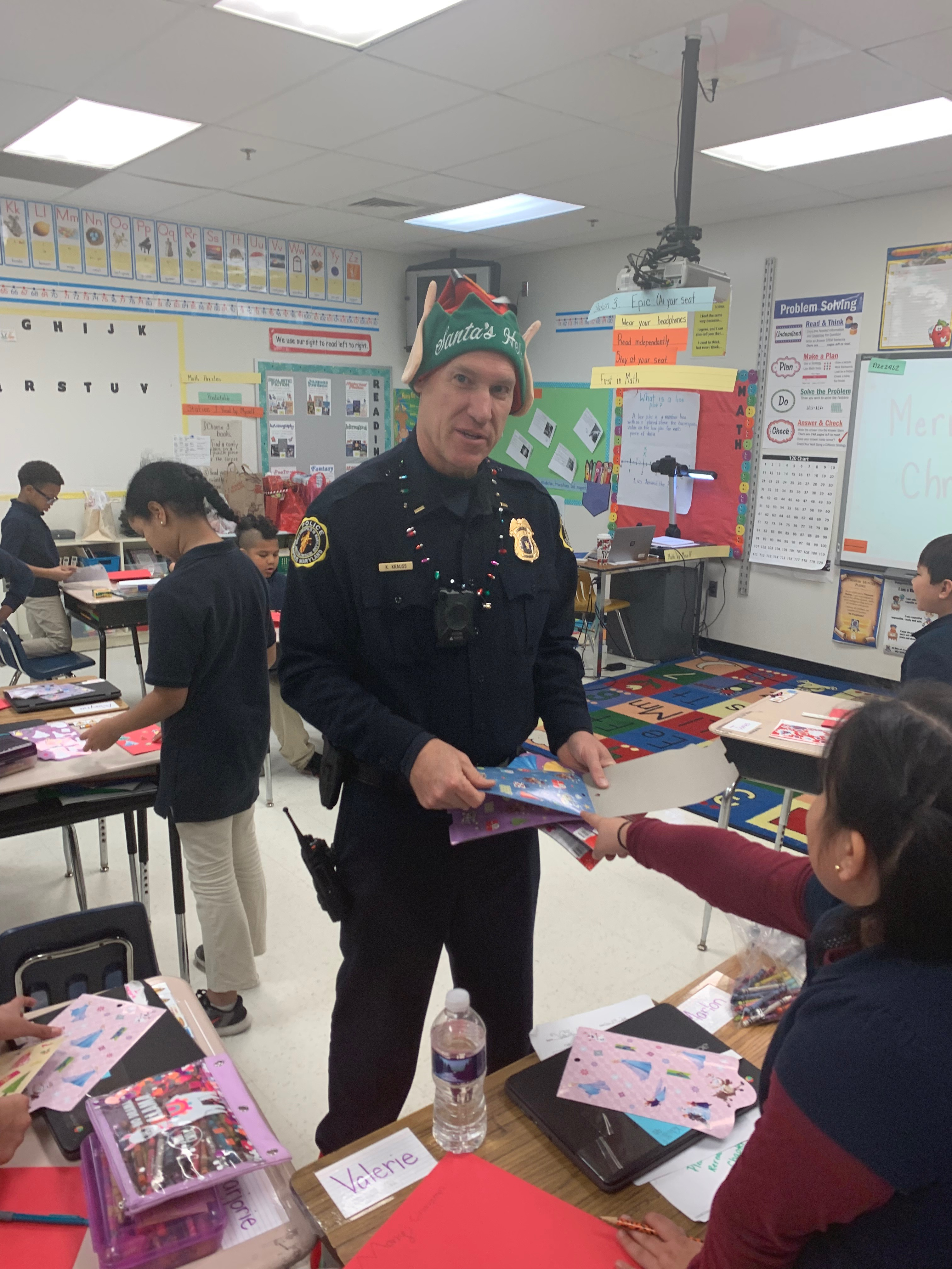 Officer wearing elf hat and shoes standing in a classroom.