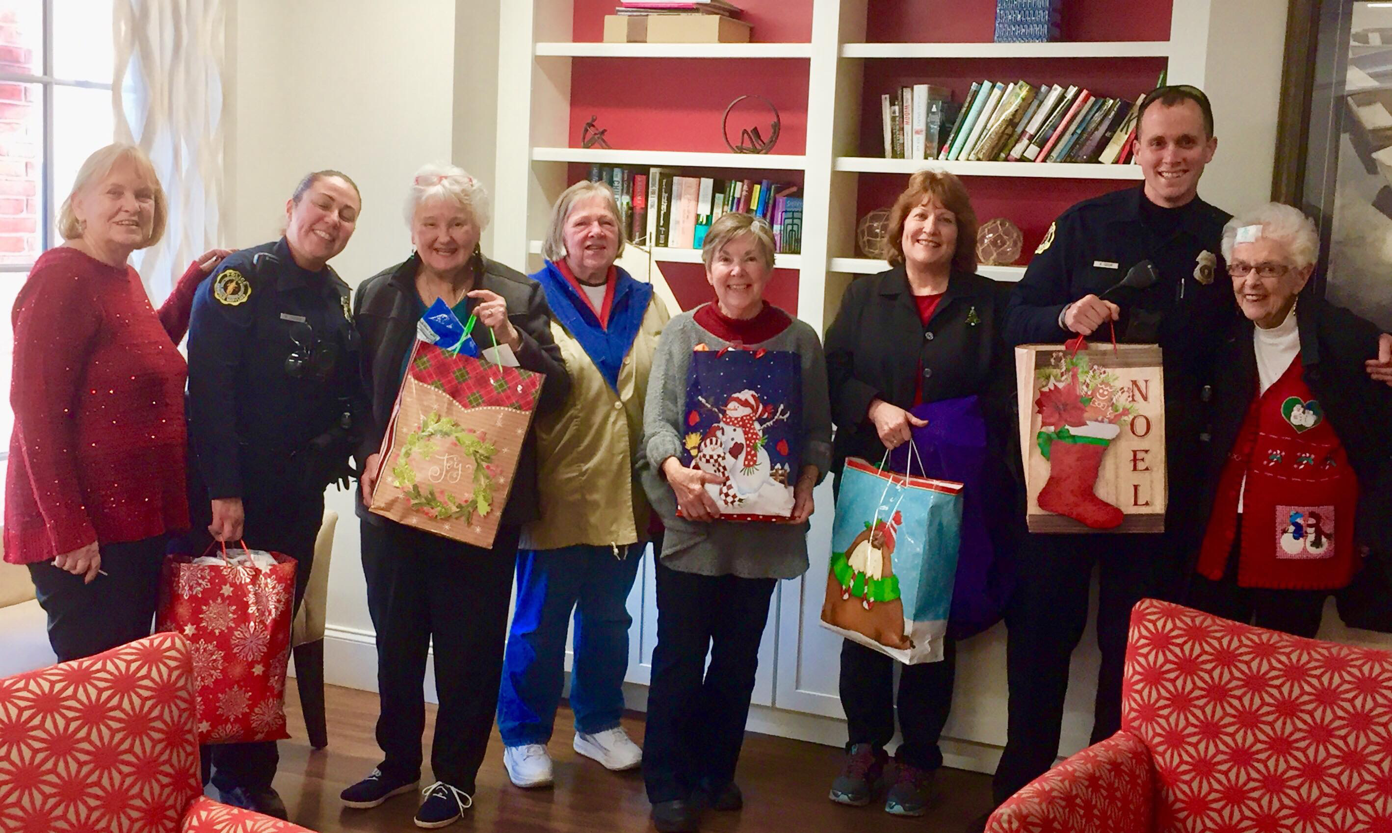 A group of people standing and holding Christmas gift bags.