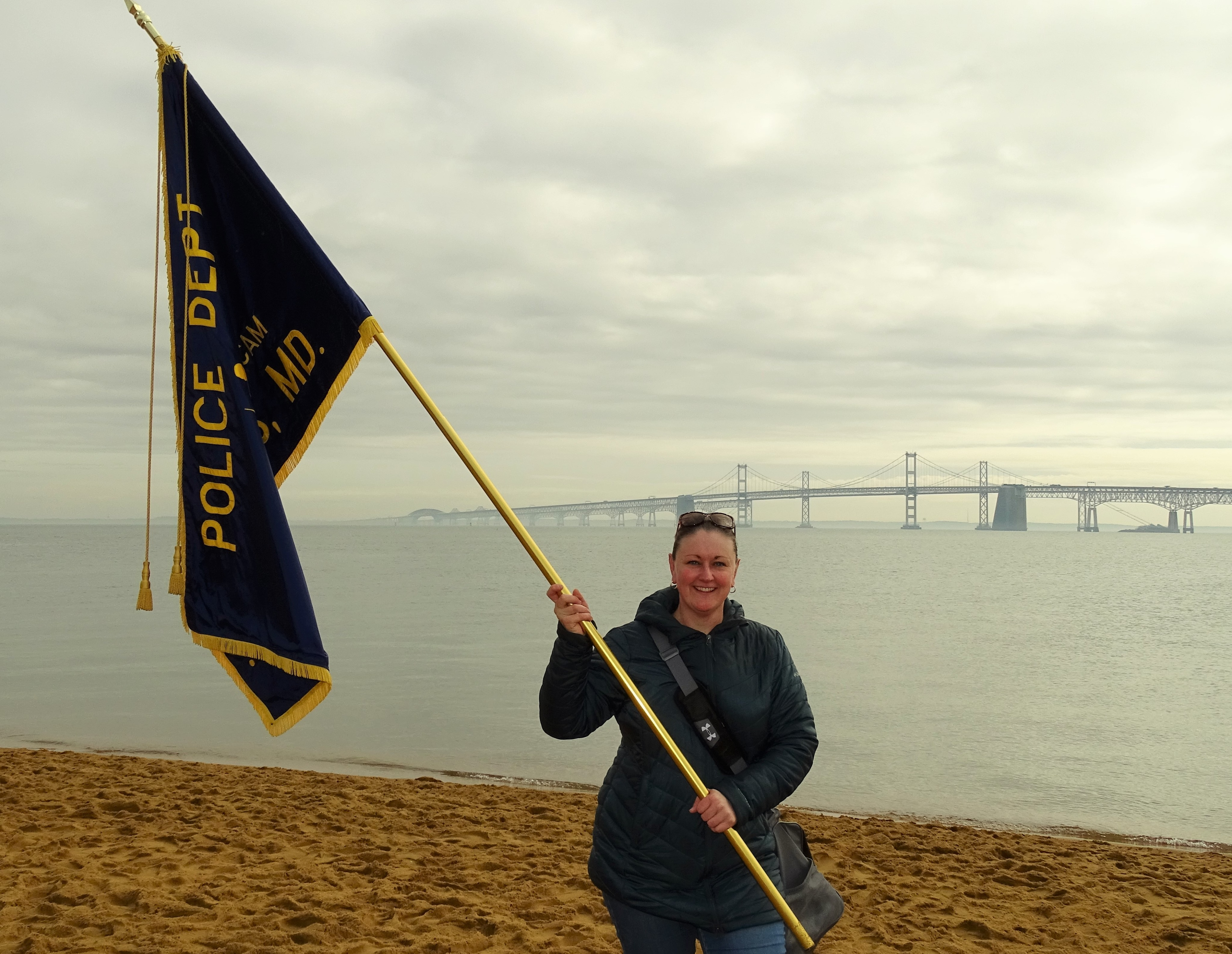 Officer holding the Annapolis police guidon on beach.