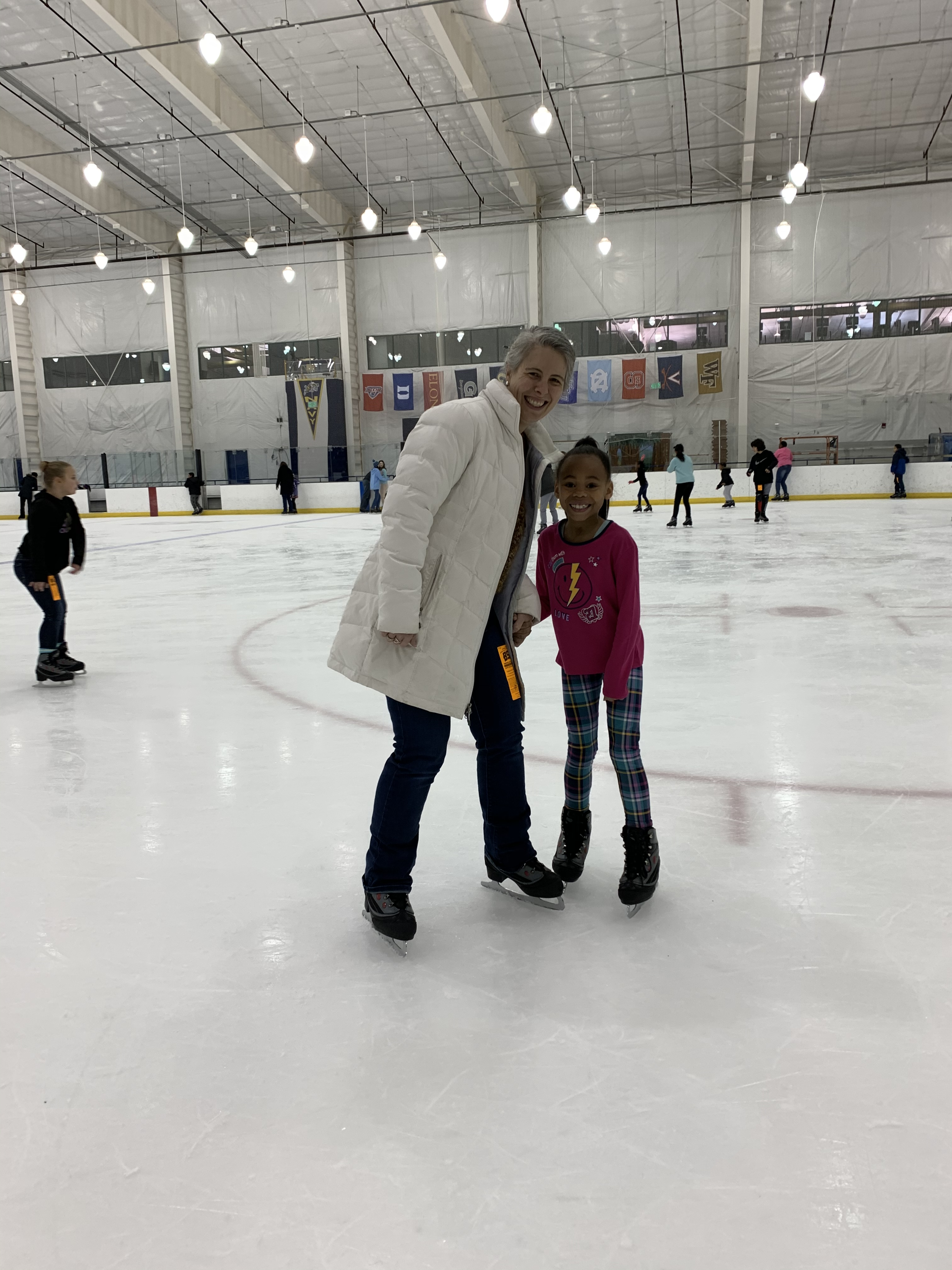Officer and child standing on an ice skating rink.
