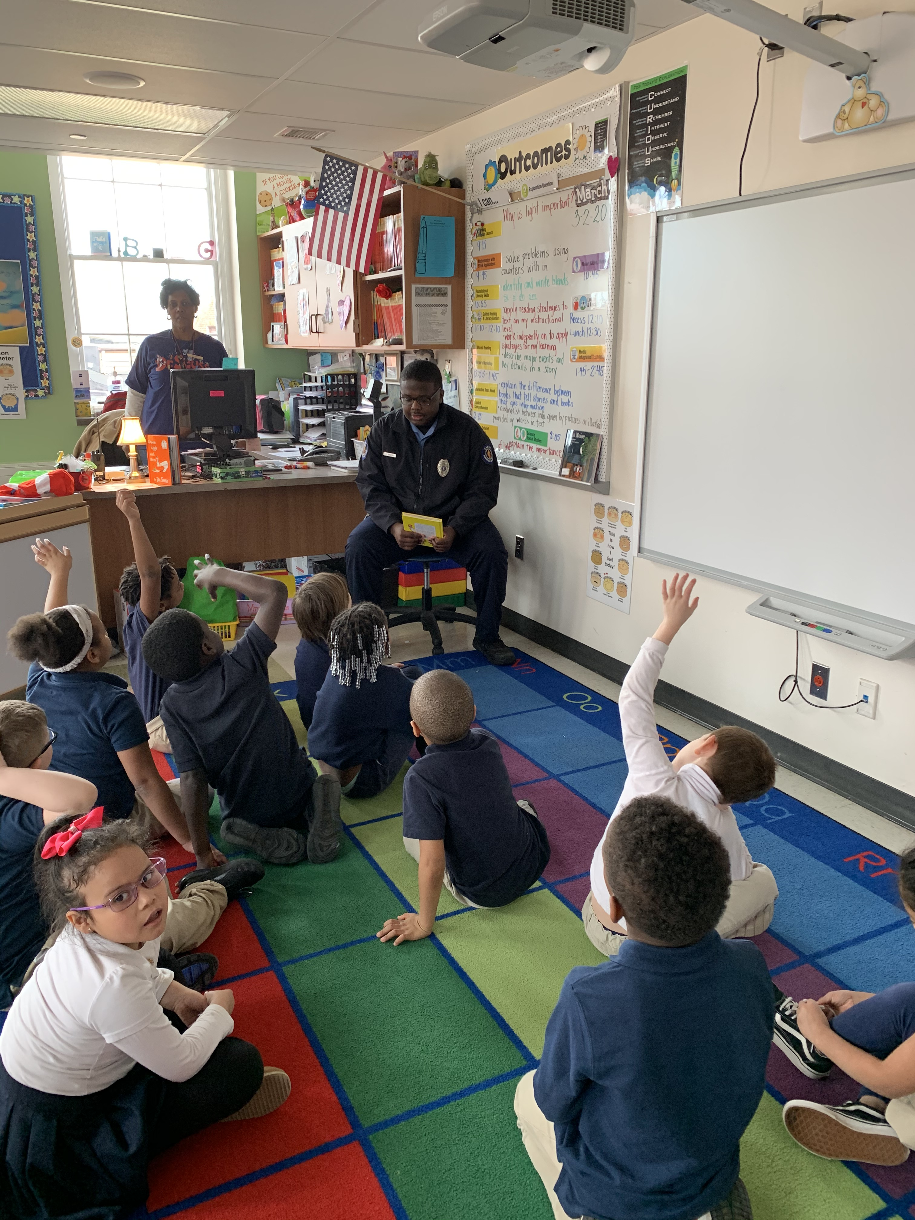 Cadet reading to a classroom full of children.