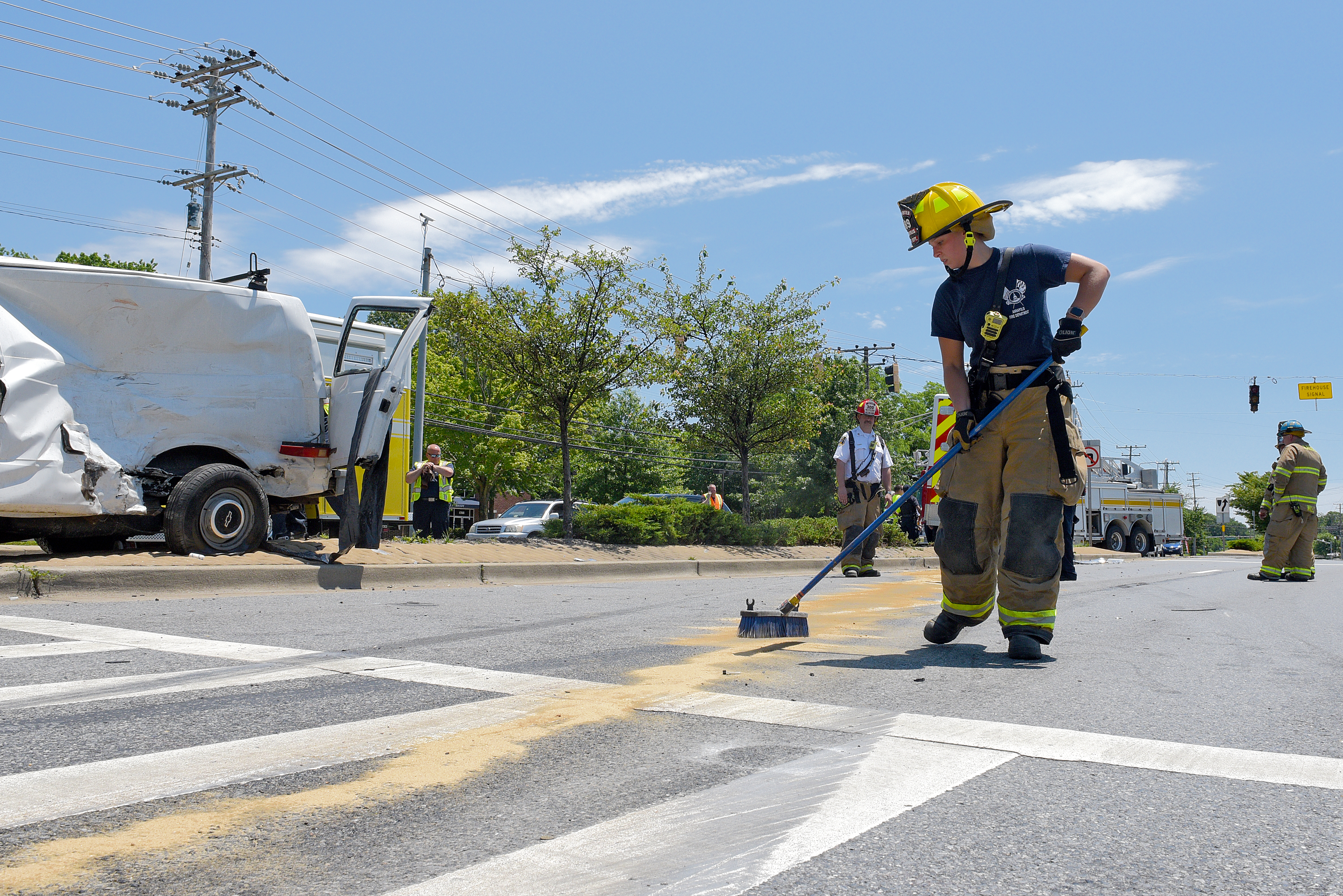Firefighter sweeping sand onto roadway
