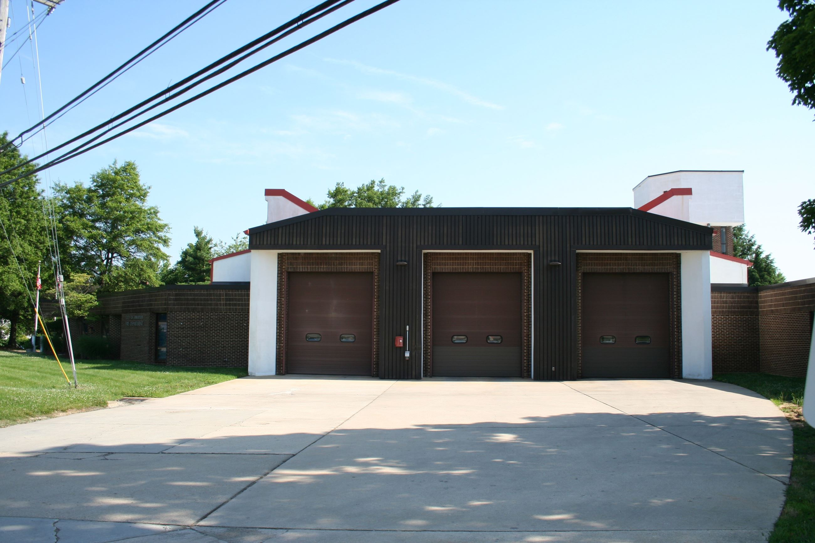 A fire station with 3 large garage doors.