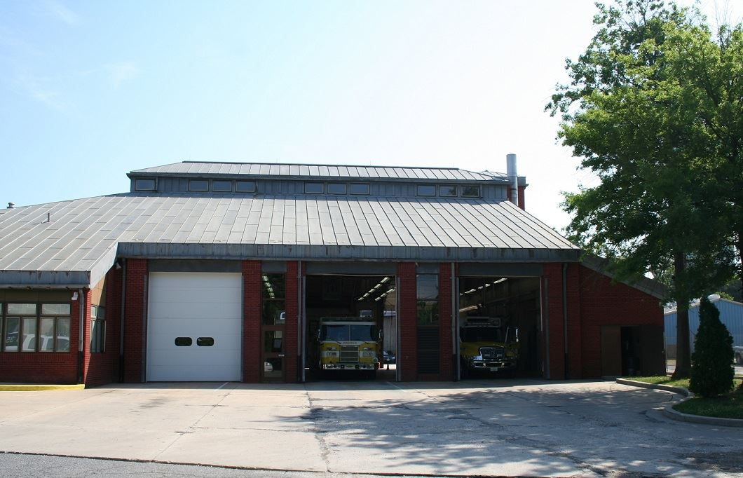 A fire station with fire trucks parked inside.