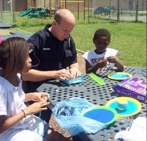 Officer engaged with children at community event.