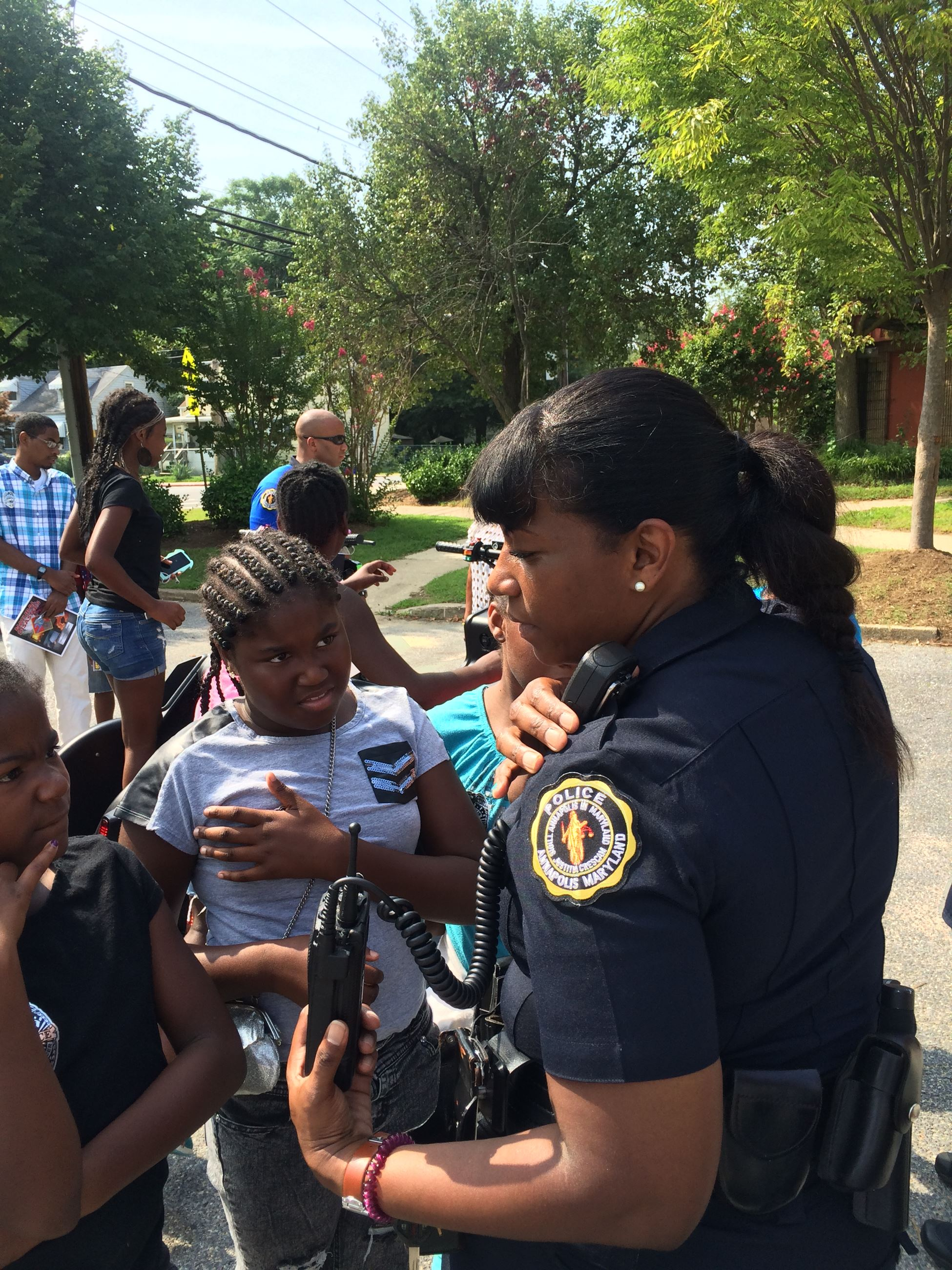 Officer answering children's questions at a community event.