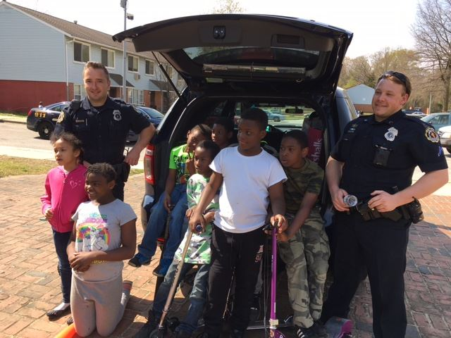 Two uniformed officers stand with children at the rear of a police car.