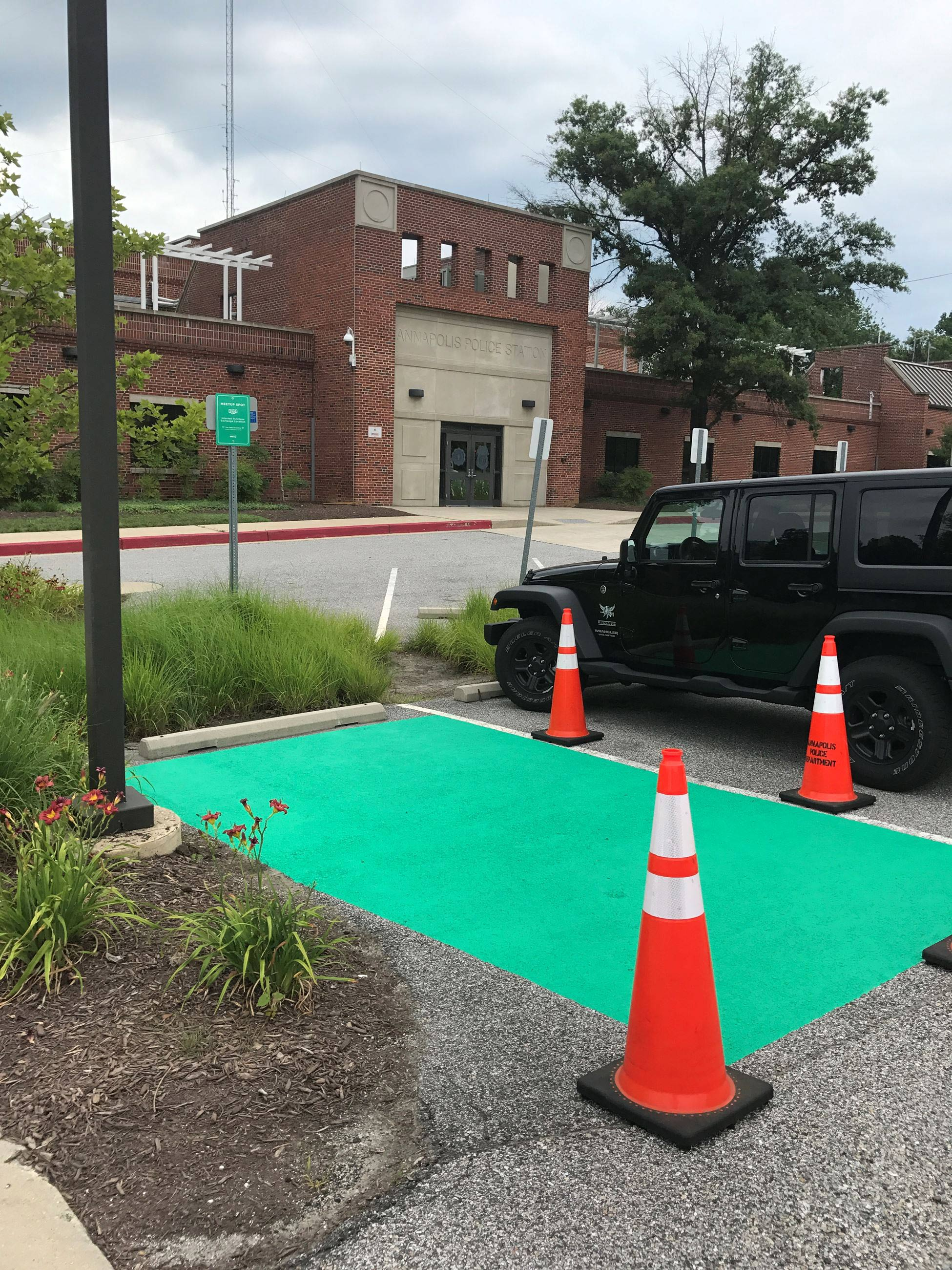 The ground of a parking space painted green for Transaction Safe Place