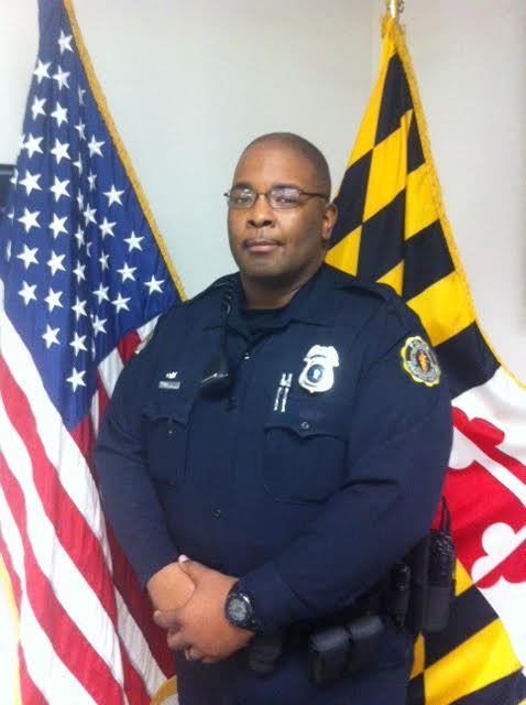 Officer Ashton in uniform in front of flags.