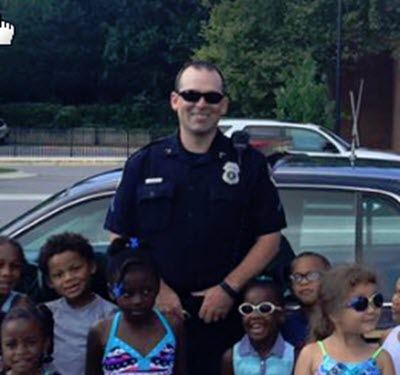 Officer Thiel standing in front a police car with a group of children.