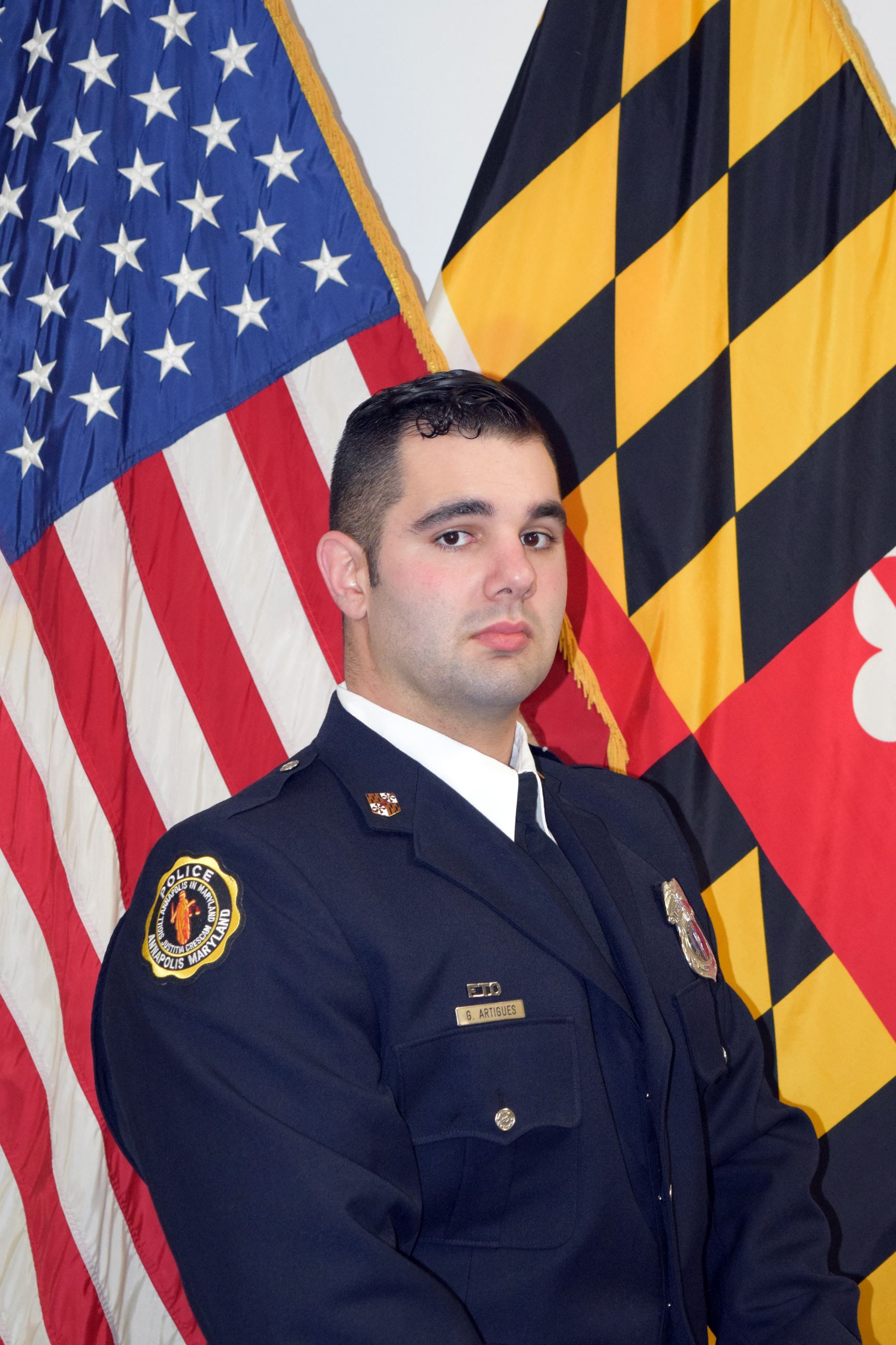 Officer Artigues in uniform in front of flags.