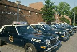 Vintage police cars parked in front of the police department.