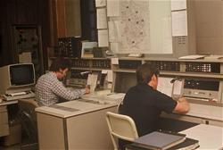 A vintage photo of people in the communications section at the police department.