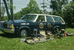 A vintage photo of a crime scene response vehicle and the supplies displayed outside the vehicle.