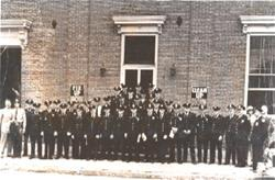 A vintage photo of a group of uniformed police and fire department officers in front of city hall.