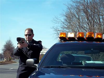 Police Officer checking speed a speed radar.