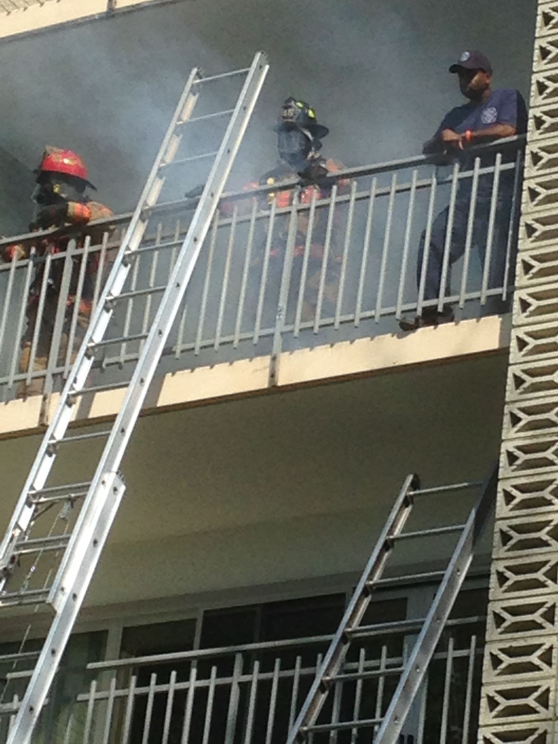 Three fire fighters standing on the second story porch of a building with smoke coming out behind them.