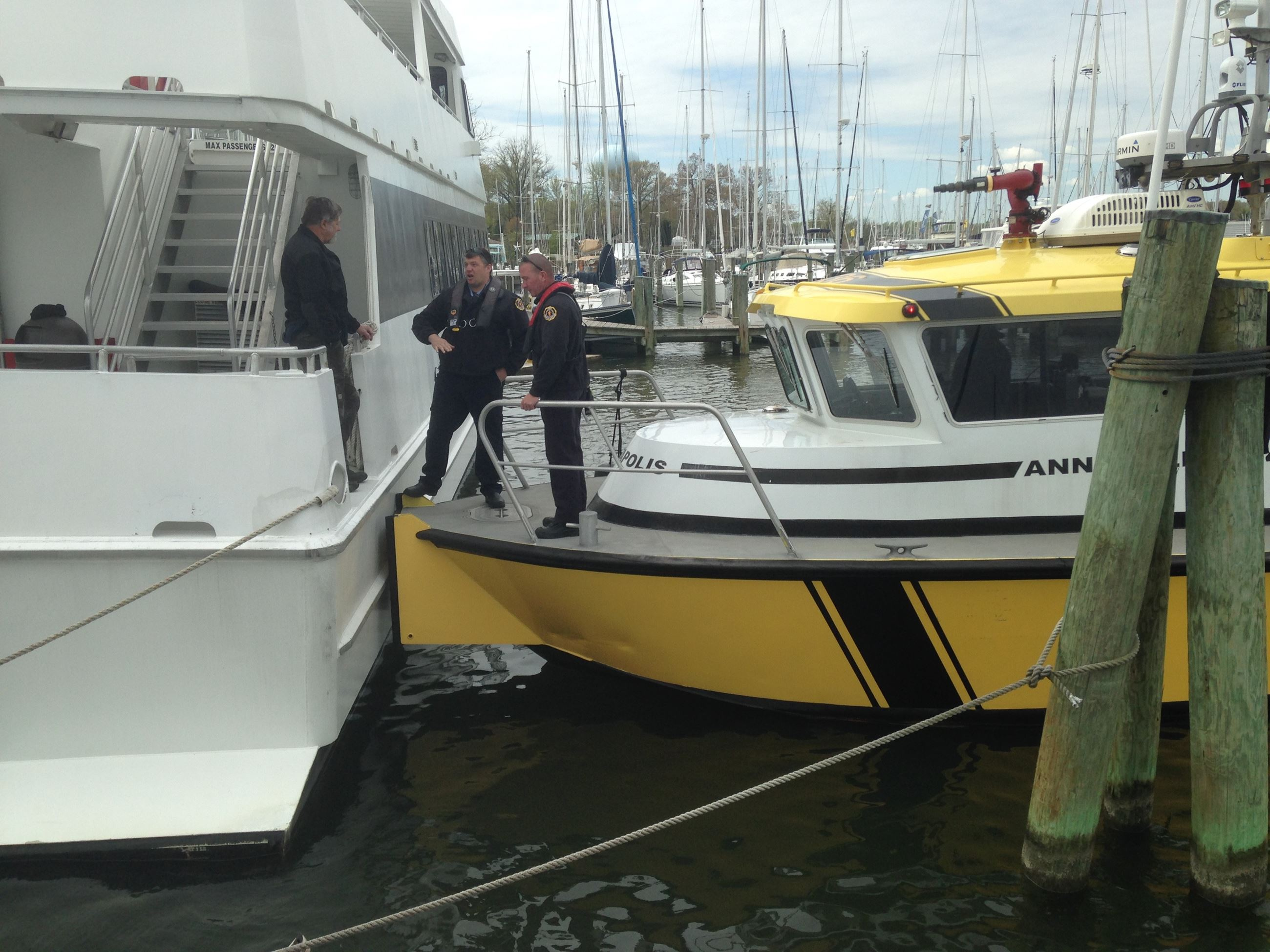 Three fire fighters boarding a boat.